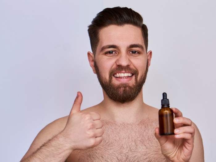 A young smiling man holding a bottle of essential oil