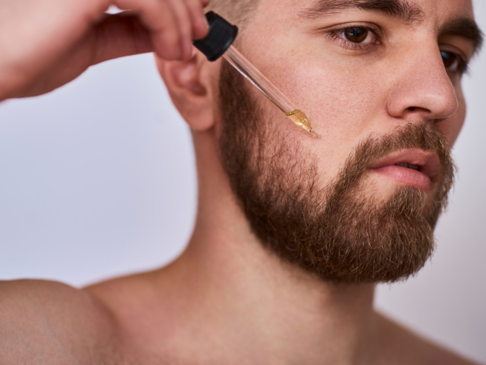 A man with a beard applying oil using a dropper