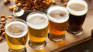 Different types of beer with a bowl of snack on a wooden table