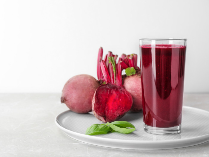 A glass of beet juice with whole beets placed on a white plate