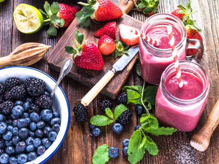 A flat-lay pic of berry smoothies kept atop a wooden platform along with a bowl of berries