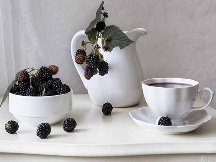 A bowl of blackberries, teapot with blackberries, and a cup and saucer of blackberry tea