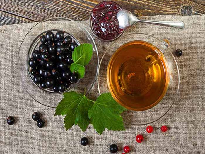 Black currant tea in a cup, next to blackcurrant fruits in a cup, and blackcurrant leaves on a table