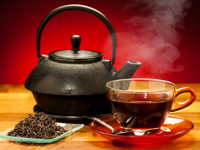 A cup of black tea, a black kettle and a plate of black tea leaves on a wooden table