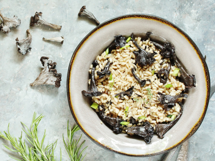Risotto in a bowl made with black trumpets and chanterelles