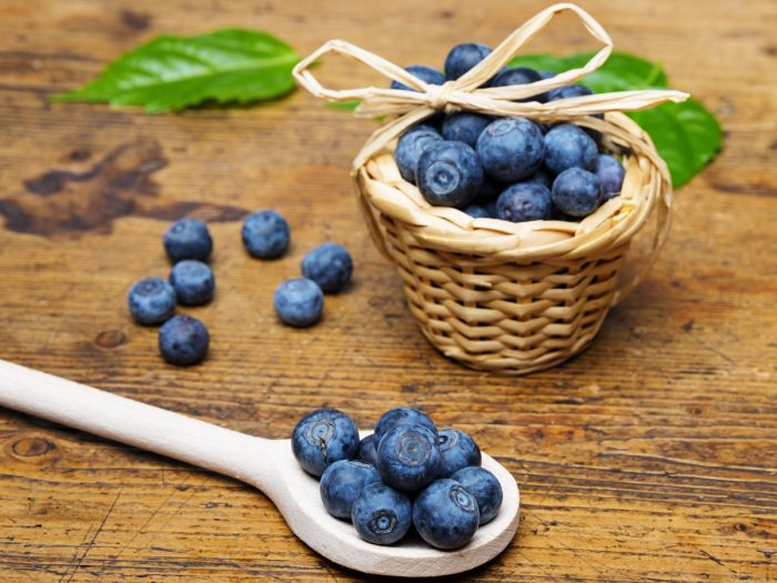 A small wooden basket and wooden spoon filled with blueberries on a wooden table