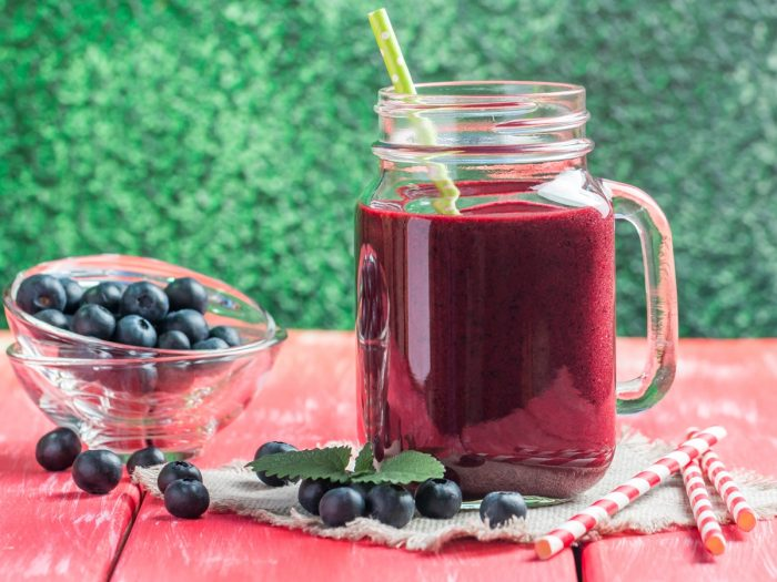 A mason jar filled with blueberry juice with few blueberries aside