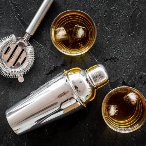 Top view of brandy cocktails with bartender tools on a slate background