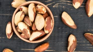 Bowl filled with Brazil nuts on a wooden background