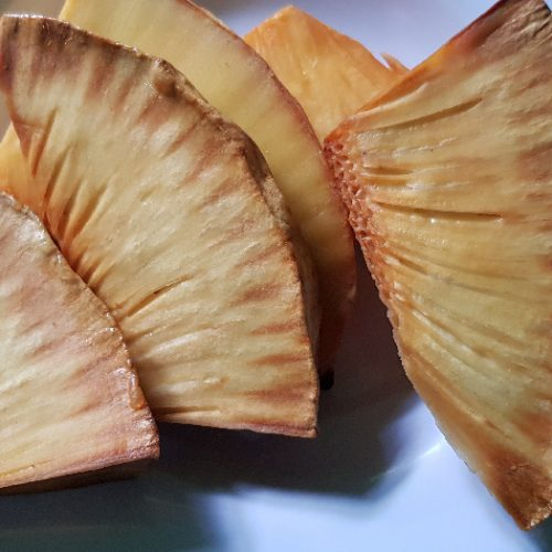 Roasted breadfruit wedges on a white plate