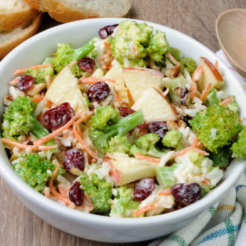 broccoli cranberry salad with sliced apples in a white bowl