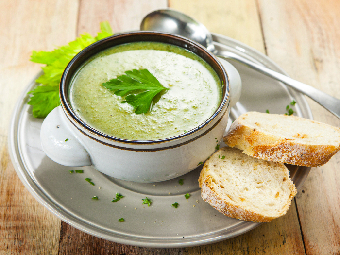 Homemade cream of celery soup garnished with celery leaves