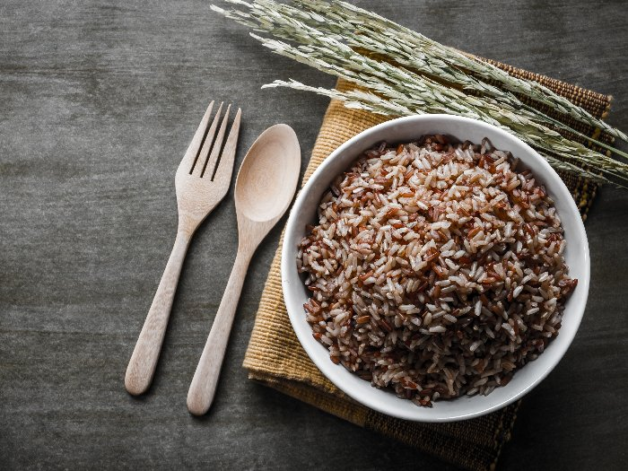 Brown/Coarse Rice with wooden spoon and fork, rice seed