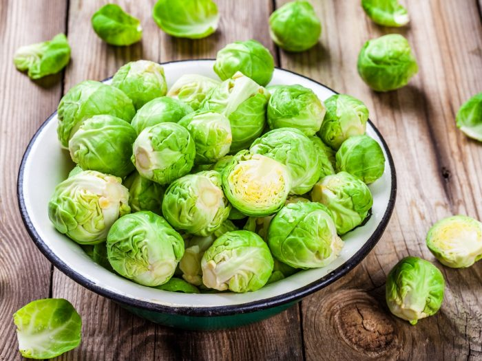 Fresh green Brussels sprouts in a ceramic bowl on a wooden table
