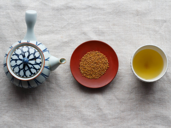 A flat lay picture of a kettle, buckwheat seeds, and buckwheat tea kept in line next to each other