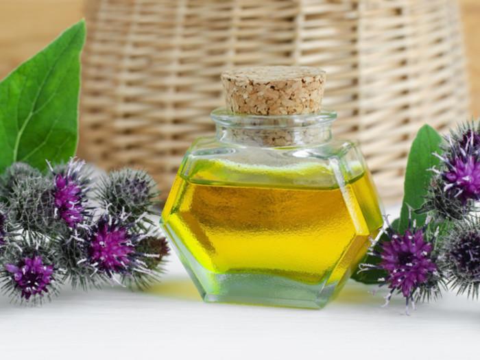 Bottle of oil surrounded by burdock flowers.