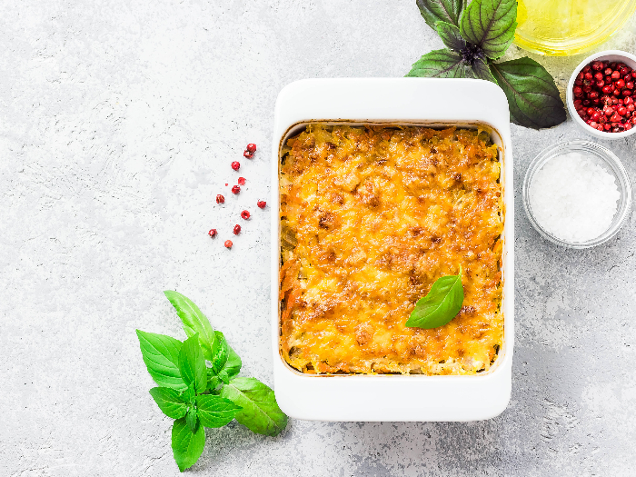 Cheesy stuffed pineapple casserole on concrete background