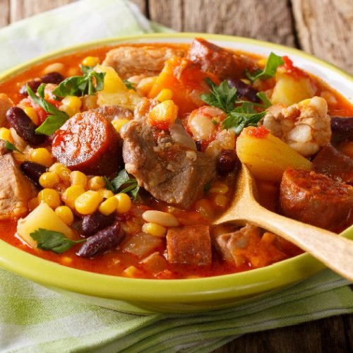 Cachupa, a slow cooked stew of corn, beans, vegetables and meat, popular in Africa in a green bowl