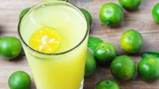 A glass of calamansi lime juice with fresh calamansi lime fruits on a wooden table
