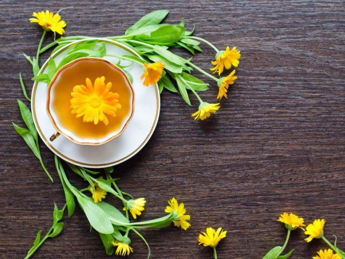 A flat lay picture of calendula tea placed on a black platform, surrounded by calendula flowers