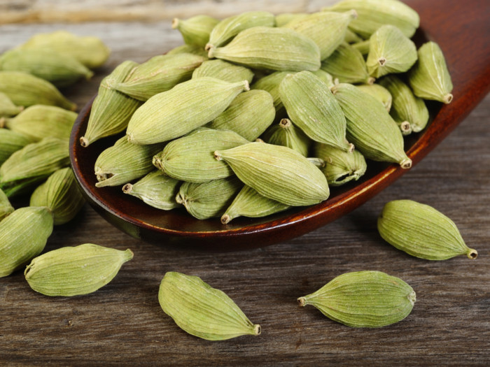 Green cardamom pods on a wooden spoon