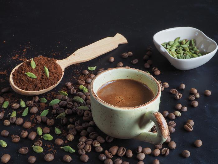 Café de cardamomo preto em uma xícara, com pó de café, pastilhas de cardamomo e grãos de café
