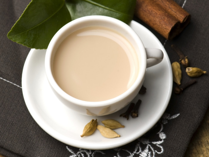 A teacup and saucer with cardamom tea with milk, and cardamom pods on the saucer
