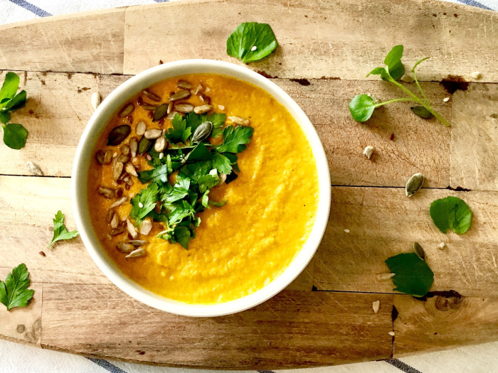 Carrot soup with coriander, parsley, and seeds in a white bowl on a wooden board.