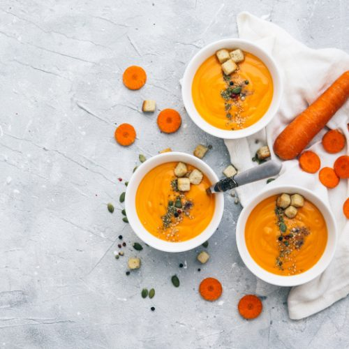 Three bowls of carrot and coriander soup topped with seeds and croutons