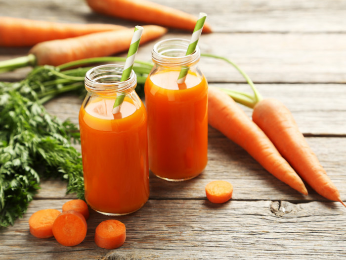 Carrots and two bottles of carrot juice on a wooden surface