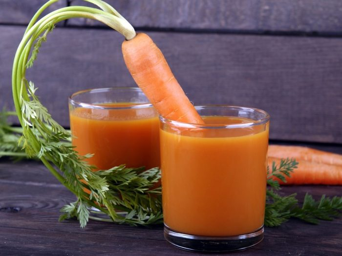 A carrot sticking out of one of the two glasses of carrot juice placed atop a black table