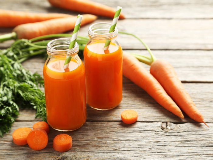 2 bottles of fresh carrot juice with straws inside, whole and halved carrots and cilantro leaves on a wooden table