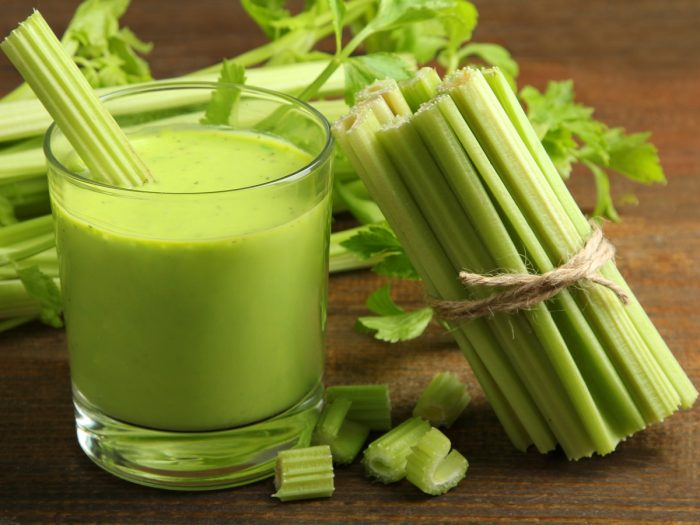 A glass of celery juice with a bunch of celery sticks on a wooden table