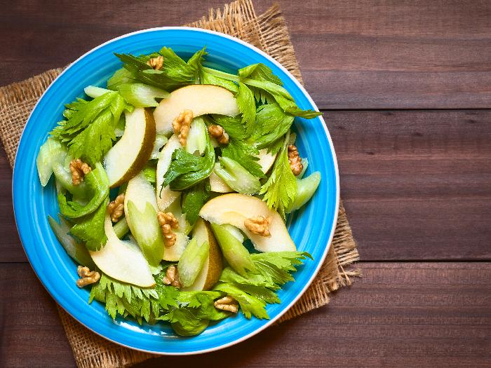 Fresh celery, pear, and walnut salad on blue plate