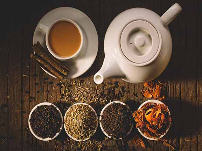 Flatline view of a kettle, a cup and saucer of tea with four small bowls of different spices.