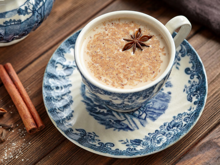 Cup and saucer of milky tea topped with star anise.
