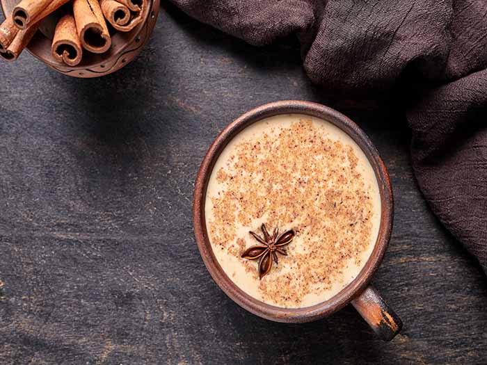 A cup of chai tea latte with cinnamon powder and star anise, with cinnamon sticks