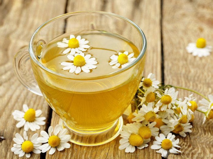 Chamomile tea in a glass cup with fresh chamomile flowers
