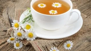 Chamomile tea in a white cup and chamomile flowers on a table