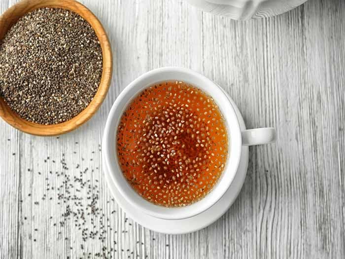 A flat lay pic of chia seed tea kept beside a bowl of chia seeds on top of a table