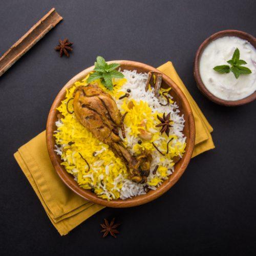 Flatline view of chicken biryani with yogurt dip on a slate background.