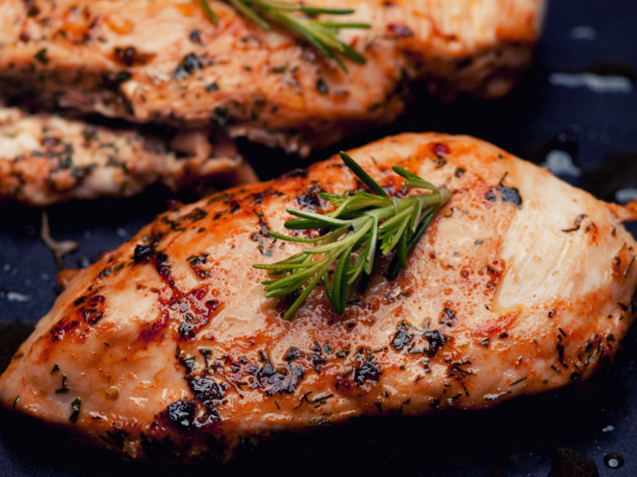 Grilled chicken breast fillets with rosemary on a dark background