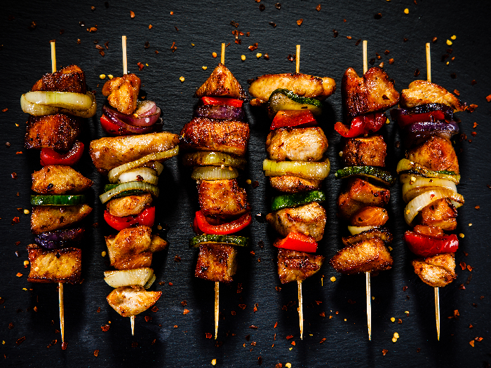 Chicken skewers with vegetables placed together on a black stone surface