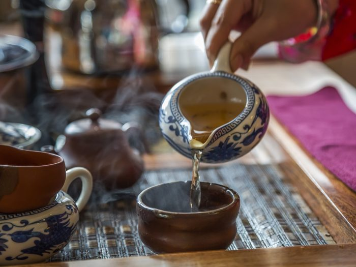 A woman pouring tea into a cup