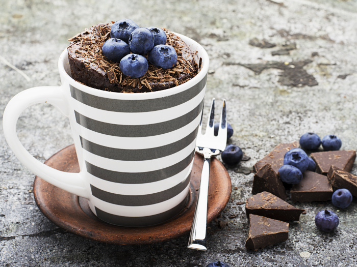 Chocolate mug cupcake with blueberries and chocolate chips in a gray striped ceramic mug on a gray background