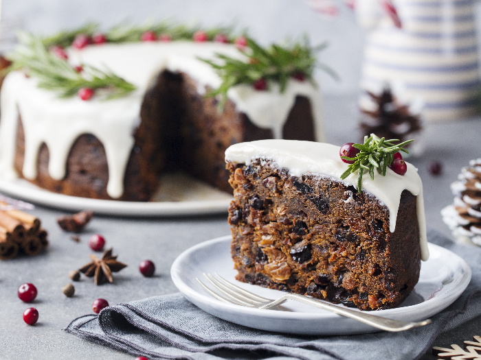 A close-up picture of Christmas fruit cake, pudding on white plate against a background of christmas decoration.