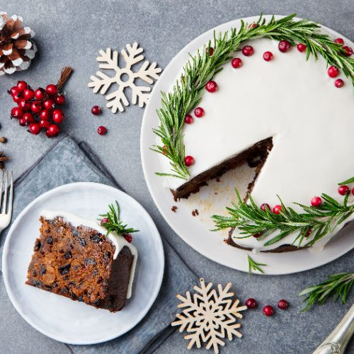 Christmas fruit cake and a slice on a white plate