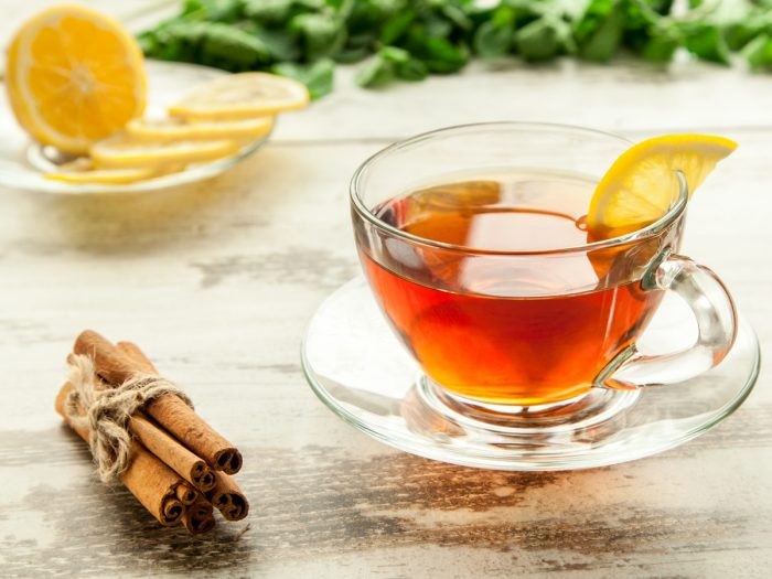 A cup of fresh cinnamon tea kept atop a table, next to a bunch of cinnamon sticks and a plate of lemon slices