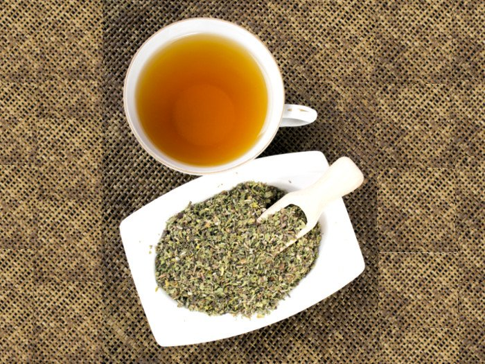 A cup filled with tea and loose leaf tea in a white bowl
