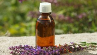 A bottle of clary sage oil with clary sage flowers